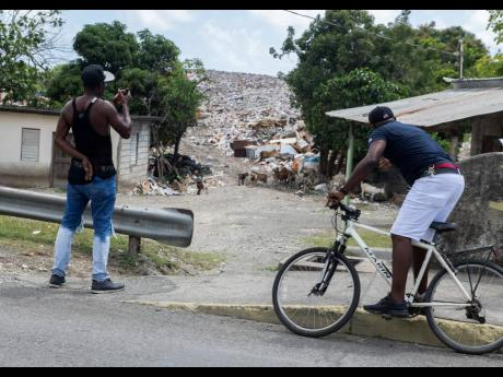 Devon Williams (left) and Bryan Malcolm look on at the unsightly, foul-smelling dump situated in the vicinity of the Morant Bay roundabout in St Thomas on Wednesday. The dump towers higher than a two-storey building on an adjacent property.