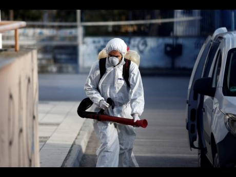 A worker wearing a protective suit enters a primary school, where a child was diagnosed with coronavirus, to spray disinfectant, in the northern city of Thessaloniki, Greece, on Thursday, February 27. The virus has spread to several countries, raising fears it could affect global economic growth.