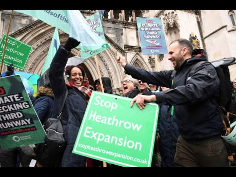 Campaigners cheer outside the Royal Courts of Justice in London, Thursday February 27, 2020 after winning a court ruling to block the plans for a third runway at Heathrow Airport on environmental grounds.