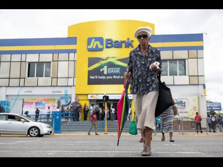 An elderly woman crosses Constant Spring Road to the Half-Way Tree Transport Centre parallel to the Jamaica National Bank yesterday. It was reported the bank suffered a major cyberattack on its systems which affected JN Bank services.