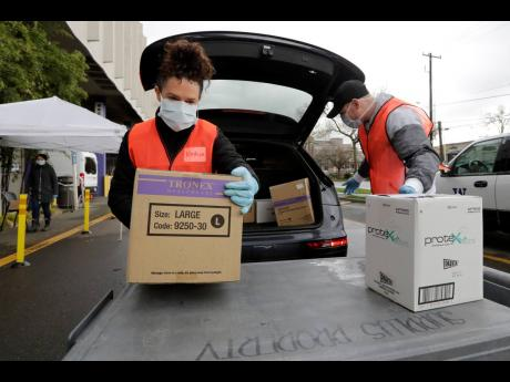 Volunteers Keshia Link (left) and Dan Peterson unload boxes of donated gloves and alcohol wipes from a car at a drive-up donation site for medical supplies at the University of Washington to help fight the coronavirus outbreak yesterday.