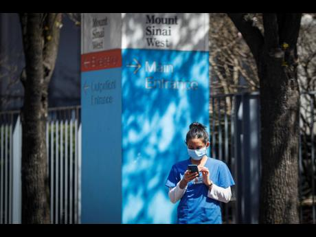 A medical worker uses her phone while wearing a surgical mask outside Mt Sinai West on Thursday, March 26, in New York.