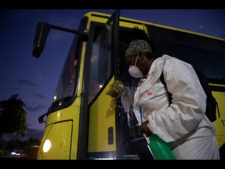 Allaeine Cooke sanitises a state-operated JUTC bus prior to passengers boarding at the North Parade bus park in Kingston on Tuesday March 24, 2020.