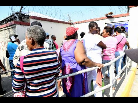 Rudolph Brown/Photographer People attending the Comprehensive Health Centre at Slipe Pen Road in Kingston on Friday form a line with little distance from each other despite the Government's policy on social distancing to avoid the spread of COVID-19.