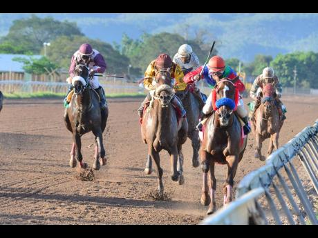 FILE HARRY'S TRAIN (right), with Dane Dawkins aboard, wins the ninth race at Caymanas Park on Saturday, March 21.