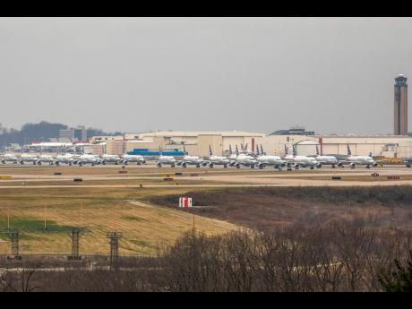 Dozens of parked American Airlines planes are parked at the Pittsburgh International Airport, on Friday, March 27, 2020, in Moon, Pennsylvania.