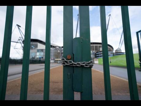 A locked gate is seen by the Etihad Stadium, where Manchester City were due to play Burnley in an English Premier League match on Saturday, March 14, after all English games were cancelled due to the spread of COVID-19.