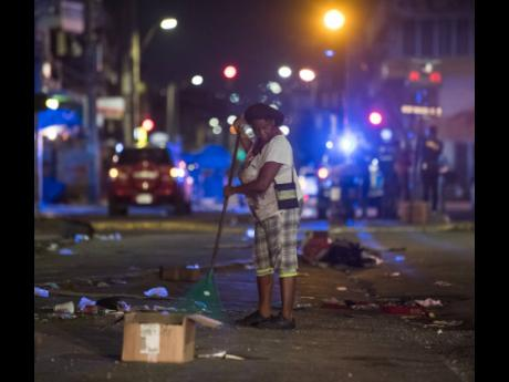 A woman cleans the streets of downtown Kingston at 8:18 on April 1, the first night of the curfew. The 10-hour measure will continue for seven days, ending on April 8.