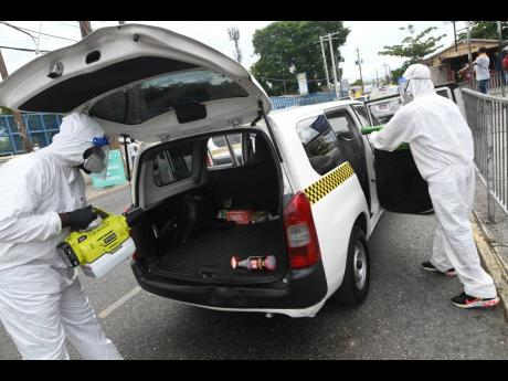 Jovan Robinson (left) and Ranniese Adam, of Mint Cleaners Ltd, sanitising taxis in Half-Way Tree, St Andrew, on Sunday. The bill was underwritten by the Ministry of Transport and Mining.
