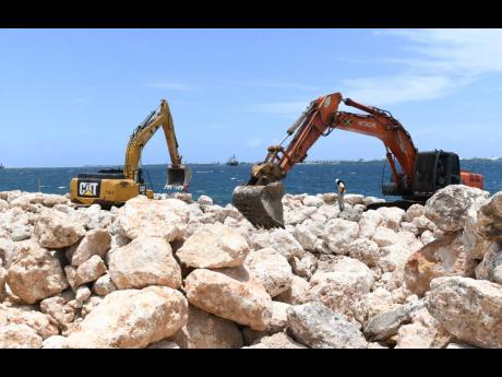 Heavy machinery manoeuvres boulders along the Kingston waterfront in the vicinity of the Rae Town fishing village. A multimillion-dollar shoreline protection wall, or stone guard, is being constructed as a buffer against sea surges.
