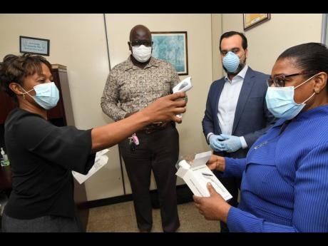 Sergio González (second right), public relations and project manager of Medimpex Jamaica Ltd, and Dwayne Francis (second left), CEO of Spanish Town Hospital, look on as Senior Medical Officer Dr Jacqueline Wright-James takes the temperature of Matron Novelette Robinson after Medimpex's donation of six infrared thermometers to the Spanish Town Hospital in St Catherine on Monday, May 11.