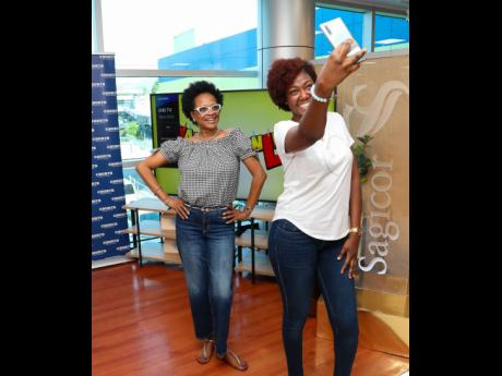 Debbie Rowe (left), merchandising manager at Unicomer (Courts) Jamaica, and Michelle-Ann Letman, public relations and corporate social responsibility manager at Sagicor Group Jamaica, pause for a quick selfie on the 'Laugh Online' set.