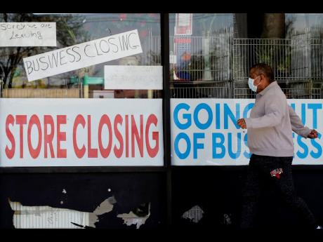 A man looks at signs of a closed store due to COVID-19 in Niles, Illinois, yesterday.