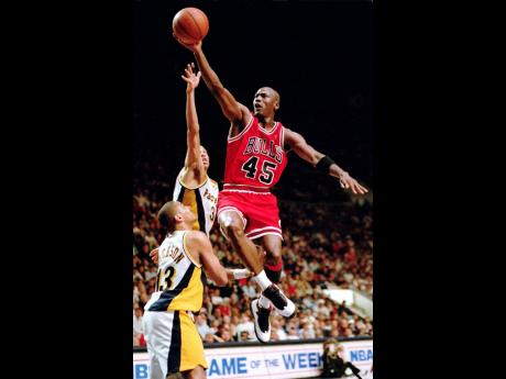 In this file photo from March 1995, Chicago Bulls guard Michael Jordan (45) flies to the hoop over the Indiana Pacers' Reggie Miller and Mark Jackson (left) during an NBA game in Indianapolis, Indiana.