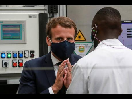French President Emmanuel Macron wears a face mask as he speaks to a worker during a visit at the Valeo manufacturer plant in Etaples, northern France, on Tuesday, May 26, 2020.