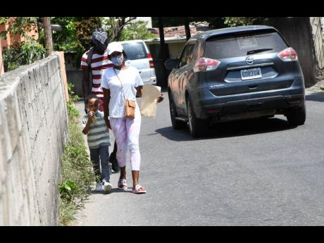 Pedestrians walk close to a boundary wall along the Cassava Piece Road in St Andrew. The corridor has virtually no sidewalks.