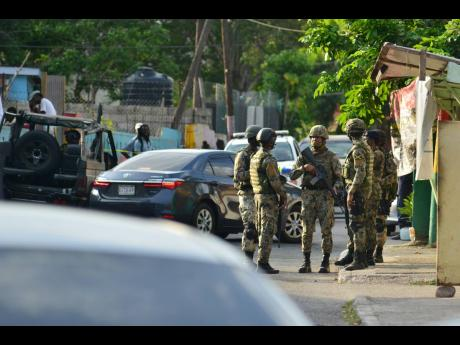 Soldiers engage in a tête-à-tête  in the wake of a fatal shooting in August Town on Wednesday. Residents allege that 44-year-old Susan Bogle was killed by a soldier.