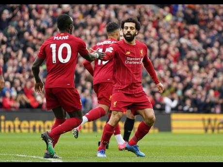 Liverpool's Mohamed Salah (right) celebrates with teammate Sadio Mane after scoring his side's opening goal during the English Premier League match against Bournemouth at Anfield Stadium in Liverpool, England, on Saturday, March 7.