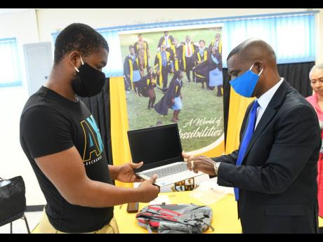 National goalkeeper Akeem Chambers, who is also a student of The Mico University College, receives a laptop and a bag from principal Dr Asburn Pinnock during the launch of the institution's students' COVID-19 relief programme yesterday. The event took