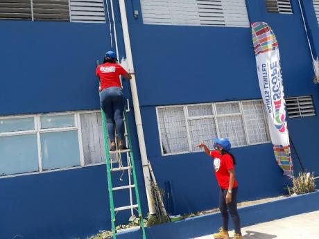 Volunteers from Kaleidoscope Paints getting the job done at the May Pen Hospital on Labour Day.
