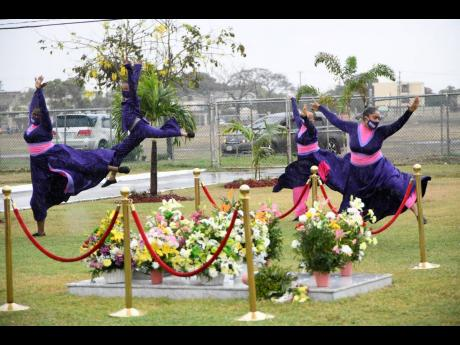 A Tivoli dance group performs in the rain in tribute to the late Edward Seaga at his tomb on Thursday. A floral tribute was laid at National Heroes Park on the first anniversary of Seaga's passing.