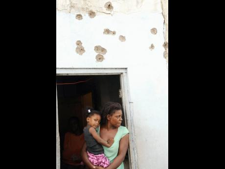 A woman and child look out from a doorway in Tivoli Gardens on May 27, 2010. The wall above was riddled with bullet holes during clashes between the security forces and armed rebels.