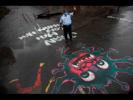 An Indian traffic policeman stands next to an artwork displayed on a road to create awareness about coronavirus during lockdown in Gauhati, India.