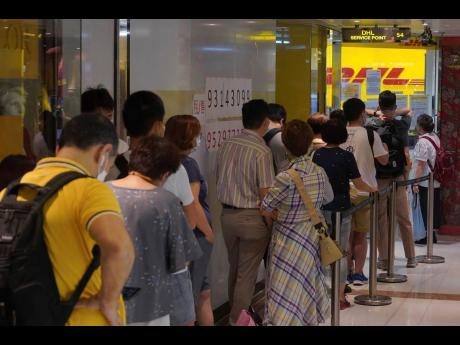People queue up outside the DHL Express store in Hong Kong yesterday.