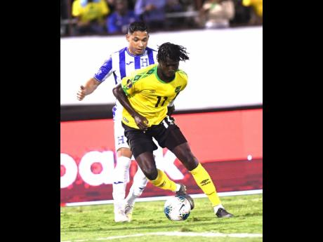Jamaica's Shamar Nicholson (foreground) dribbles ahead of Honduran player Emilio Izaguirre in their Concacaf Gold Cup match held at the National Stadium recently.