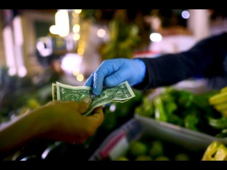 In this March 19, 2020 photo, Jorge Otero, owner of a fruits and vegetables stand, wears gloves as he exchanges cash with a customer.