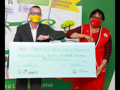 Nestlé Jamaica Country Manager Daniel Caron (left) and Hope Monroe, president of the Jamaica Red Cross Society, share in a photo op after the signing of the partnership between the two entities. Nestlé Jamaica has donated more than $12.8 million towards