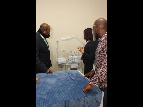 Kimisha Walker demonstrates one of several high-end machines that, among other things, removes impurities from the skin, to Minister Bartlett. Looking on is Garth Walker.