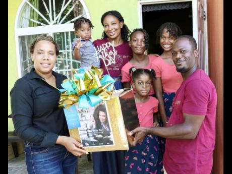 Howard Fearon (right) is surrounded by his family as he accepts the specially prepared meal from Ruchelle    Dodd-Reid (left), personal banking officer, Sagicor Bank. From second left are his young son, Howard Fearon Jr; his     wife, Kadian Staple-Fearon