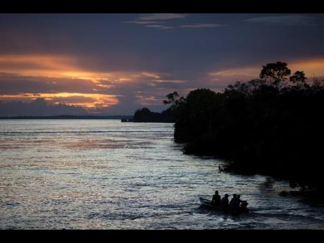In this May 22, 2014 photo, a small boat navigates on the Solimoes River near Manaus, Brazil.