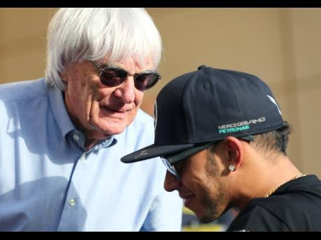 FILE  In this Thursday, April 16, 2015 file photo, Bernie Ecclestone (left), president and CEO of Formula One Management, talks to Mercedes driver Lewis Hamilton ahead of the Bahrain Formula One Grand Prix at the Formula One Bahrain International Circuit i