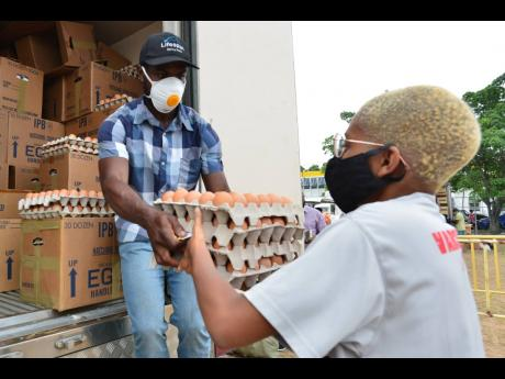 A vendor hands eggs, at $500 per tray, to a shopper at a RADA farmers' market at the agricultural authority's Old Hope Road headquarters on Thursday, May 21.