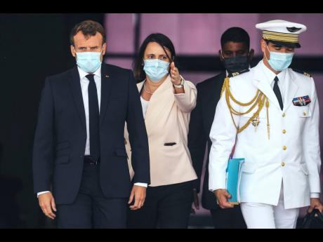 French President Emmanuel Macron (left) wears a face mask as he arrives at Nouakchott International Airport on Tuesday to attend a G5 Sahel summit.