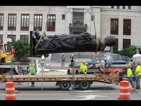 Workers remove the Christopher Columbus statue from the Broad Street side of Columbus City Hall in Columbus, Ohio, USA, yesterday. The city says it will be replaced with a different statue or artwork that reflects diversity.