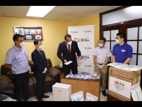 Minister of Health, Dr Christopher Tufton (centre), examines surgical masks and other medical equipment donated by the Association of Chinese Enterprises in Jamaica. Looking on are (from left) Jing Sun of JISCO Alpart Jamaica, Andy Deng of Huawei Technolog