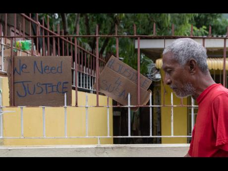 A man walks by cardboard signs memorialising the death of 43-year-old Susan Bogle in August Town, St Andrew. Residents have alleged that Bogle was killed by a soldier.