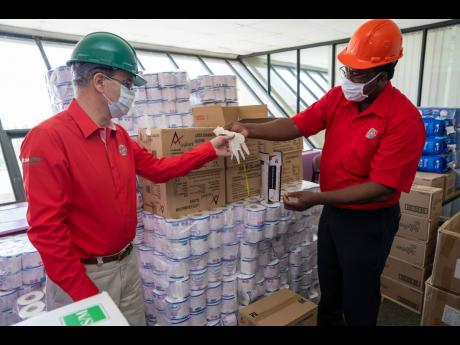 RUBiS Energy Jamaica Limited's Chief Executive Officer, Alain Carreau (left), and Human Resource Manager Donnovan Dobson inspect the quality of sanitation products and personal protective equipment in stock at the company's Rockfort, Kingston warehous