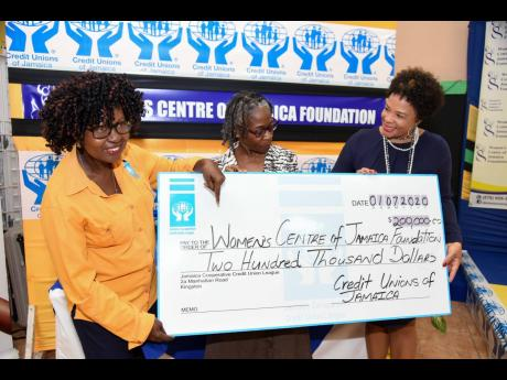 Chairperson of the Women's Centre of Jamaica Foundation (WCJF), Debby Ann Brown-Salmon (right), and executive director, WCJF, Dr Zoe Simpson (centre), receive a cheque valued at $200,000 from group marketing and communications manager of the Jamaica Co-o