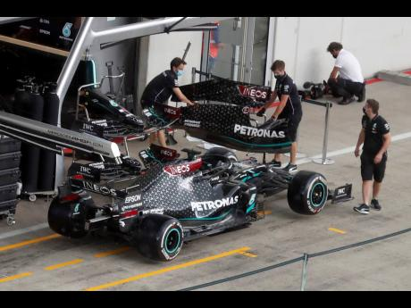 Mercedes technicians work around Lewis Hamilton's car at the Red Bull Ring racetrack in Spielberg, Austria, yesterday.