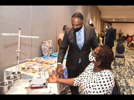 Omar Sweeney, managing director of the Jamaica Social Investment Fund, listens as Janet Madden shares information on her sewing business at the ICDP Enterprise Development Project grant awards ceremony at The Jamaica Pegasus hotel yesterday.