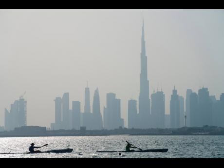 Kayakers race in front of the Burj Khalifa, the world's tallest building, off the coast of Dubai, United Arab Emirates, on June 19, 2020. Dubai has begun allowing organised sports competitions to take place after locking down over the coronavirus pandemi