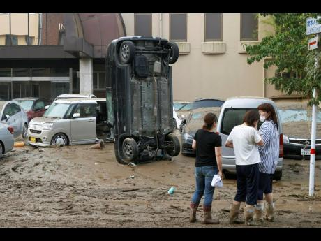 A car stands vertically on a muddy road after being washed away by flood, in Hitoyoshi, Kumamoto prefecture, southwestern Japan, Sunday, July 5, 2020. Heavy rain in the Kumamoto region triggered flooding and mudslides Saturday and left dozens still being s