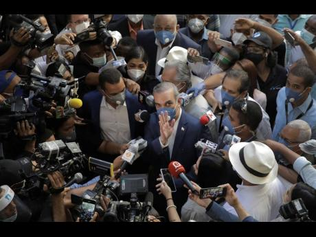 Luis Abinader, presidential candidate of the opposition Modern Revolutionary Party, greets the crowd while he is surrounded by journalists at a voting centre during the presidential elections in Santo Domingo, Dominican Republic, on Sunday.