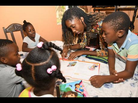 Gizzel Young (second right), a student of The Mico University College, has transformed her living room into a classroom for children displaced by COVID-19. What started with the assistance of one child increased to 10 on a shift system at Young's Carr Hi