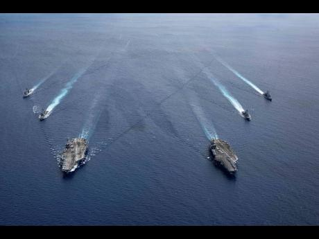 In this photo provided by the US Navy, the 'USS Ronald Reagan' (CVN 76) and 'USS Nimitz' (CVN 68) Carrier Strike Groups steam in formation in the South China Sea on Monday, July 6. China, that same day, accused the US of flexing its military muscle