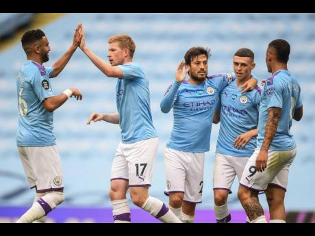 Manchester City players celebrate after scoring their second goal during the English Premier League match between Manchester City and Newcastle at the Ethiad Stadium in Manchester, England, Wednesday, July 8, 2020.